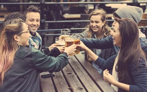 Group of friends enjoying a beer at pub in London, toasting and laughing. They are four girls and two boys in their twenties.