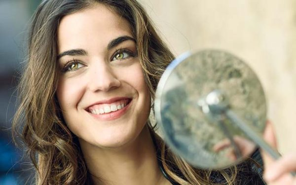 Woman looking in a motorbike's mirror, smiling and wearing casual clothes
