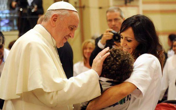 Papa Francesco accarezza un bambino durante la visita ad Assisi, 4 ottobre 2013. ANSA/ CROCCHIONI