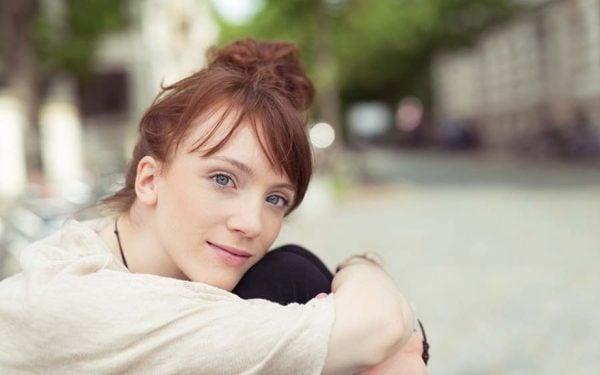 schöne junge frau mit blauen augen sitzt entspannt draußen in der stadt