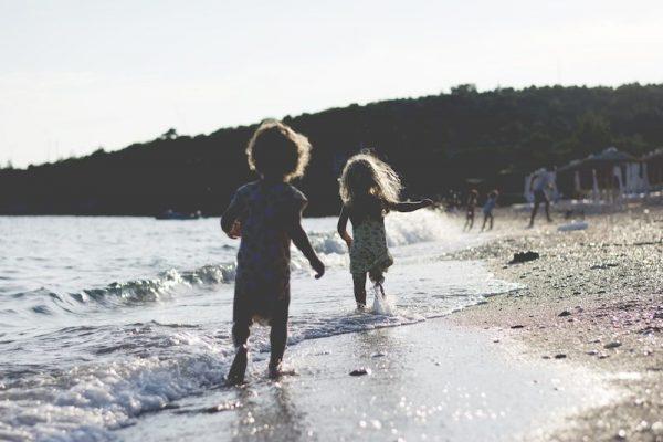 Little barefoot girl and boy running across the beach